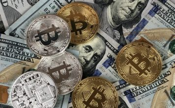 Golden and silver bitcoins on US dollars